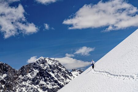 Mountaineer on snow slope in front of blue sky hiking towards snowy alpine peaks