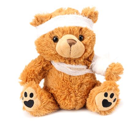 Spielzeug-Teddybär mit Verband isoliert auf weißem Hintergrund