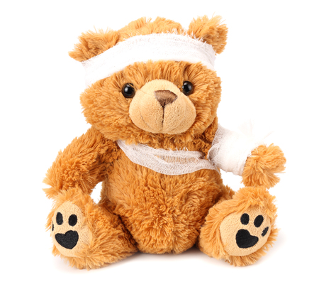 toy teddy bear with bandage isolated on white background