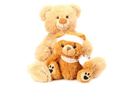 Dos osos de peluche de juguete con vendaje aislado sobre fondo blanco.