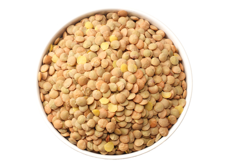 lentils in a white plate isolated on white background. top view