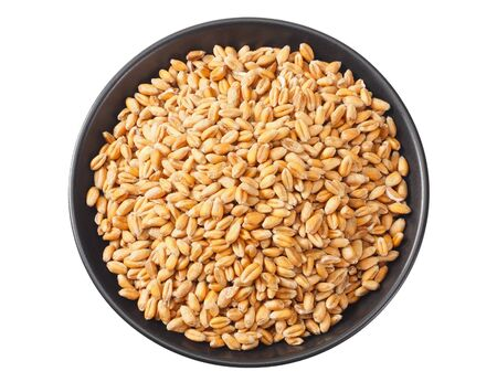 wheat grains in a black plate isolated on white background. top view