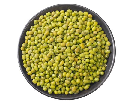 green mung beans in a black plate isolated on white background. top view