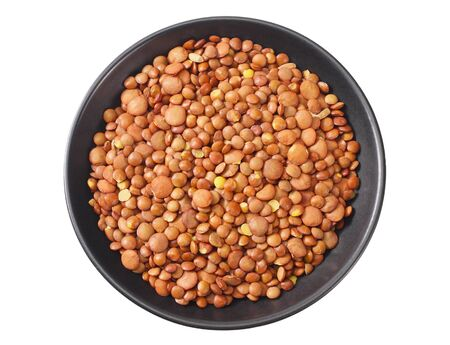 Pile lentil in black bowl isolated on white background. Top view.