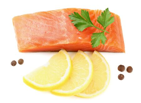 Red fish. Raw salmon fillet with parsley, peppercorns and lemon isolate on white background. Top view Reklamní fotografie
