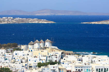 whitewashed: Mykonos windmills and white-washed houses agains the sea