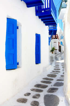 narrow street in Mykonos with white-washed houses