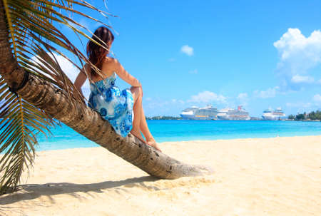 woman sitting on a bending palm tree looking at the cruise ships in the caribbean destination port