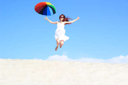 carefree girl with a rainbow umbrella jumping flying on vacation