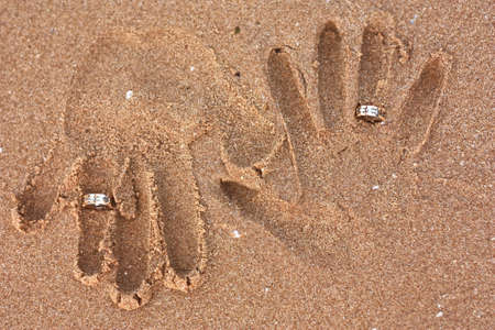 honeymooners handprints in the sand with wedding rings photo