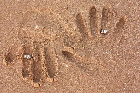 honeymooners: reci�n casados ??huellas en la arena con los anillos de boda