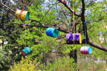 feeders: colorful bird feeders made of cans and tins