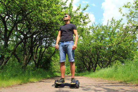 young man riding electrical scooter - hoverboard, gyro scooter, smart balance wheel