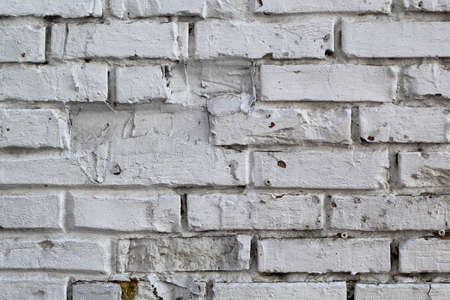 white brick wall with uneven and missing stones for background