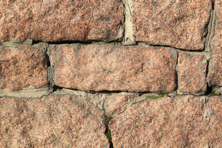 old rustic brown granite wall with uneven stones for background Stock Photo