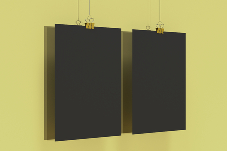 Two blank black posters with binder clip mockup on yellow background. Poster or paper sheet template. 3D rendering illustration Stock Photo
