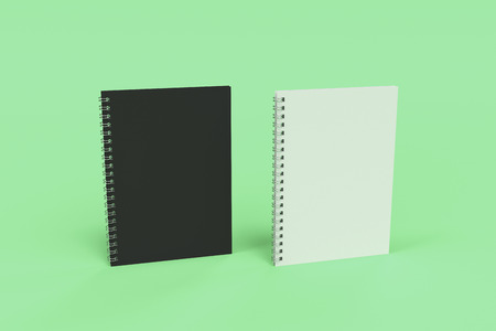 Two blank notebooks with black and white covers and metal spiral bound on green background. Business or education mockup. 3D rendering illustration