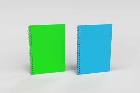 Two blank notebooks with green and blue covers and metal spiral bound on white background. Business or education mockup. 3D rendering illustration Stock Photo