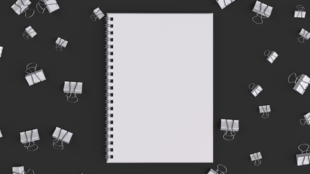 Blank spiral notebook with white binder clips on black table. Business, education or office mockup. 3D rendering illustration. Stock Photo