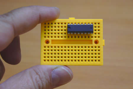 User holding a yellow protoboard with an integrated circuit chip mounted on it