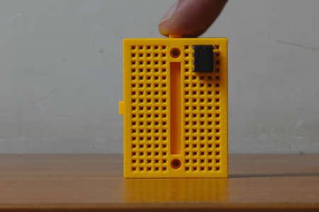 A user tapping on a vertical yellow colored protoboard with an ic chip