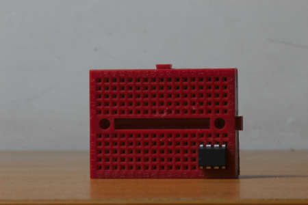 A horizontal red protoboard wit an ic mounted
