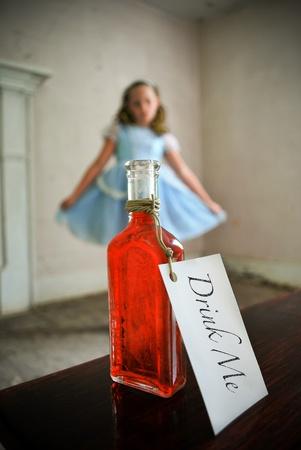 pocion: Alice mirando una botella de poci�n desde una distanciaAlicia en el pa�s de las maravillas Editorial