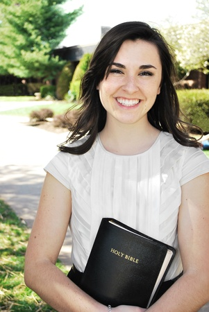 disciple: Young women smiling while holding a BibleYoung Woman Holding a Bible Stock Photo