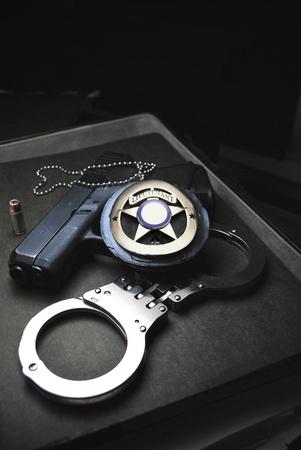 pistolas: Herramientas del comercio en la aplicaci�n de la ley, insignia, esposas y armas de fuego y proteger & servir Foto de archivo