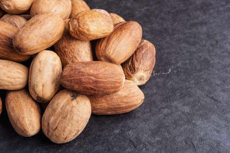 Nutmeg on dark stone background photo