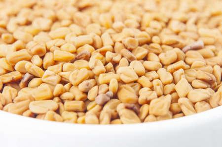 fenugreek: Fenugreek seeds in white bowl on white background Stock Photo