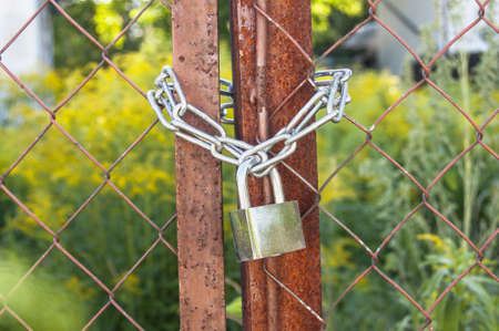 constrain: A padlock on a steel chain link fence