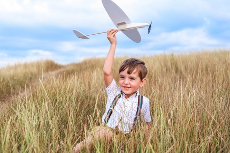 Happy boy holds a little plane and smiling. He imagines himself as a pilot. Concept of childs dreams that will come true. Stock fotó