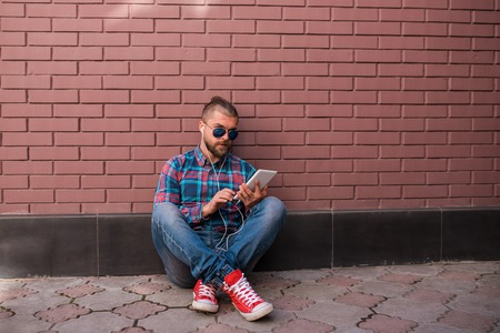 Handsome hipster guy in trendy apparel working on digital tablet. Attractive man with headphones looking at camera and holding touch pad in his hands.