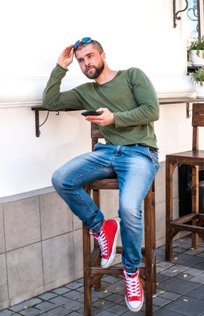 Attractive young hipster guy sitting in cafe with smart phone, He is chatting with friends. Imagens