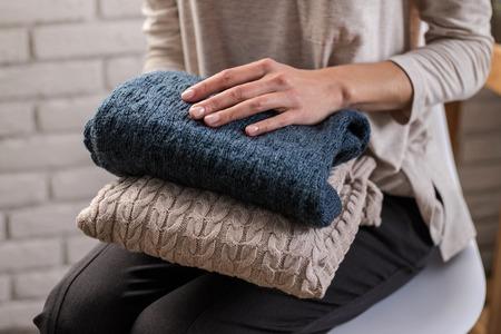 Mains de femme tenant des vêtements tricotés. Fermer. Concept de maison confortable. Banque d'images