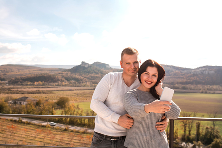 Happy young couple making selfie against the mountains. They smiling and hugging. Concept of travelling, freedom and love.