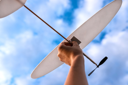 Little white toy plane in woman's hand in sky. Concept of reaching goals.