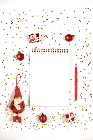 Creative Christmas composition with notepad and decorations, confetti, gifts and balls. Flat lay style, copy space.