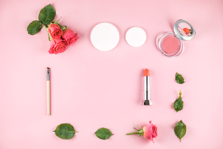 Flat lay composition with lipstick, blush, sponges, brush and flowers on pink background. Top view, copy space. Stock Photo