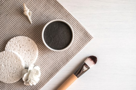 Composition with natural black cosmetic facial mask in ceramic bowl, brush, sponges, white flower and shell on rustic background. Flat lay. Stock Photo