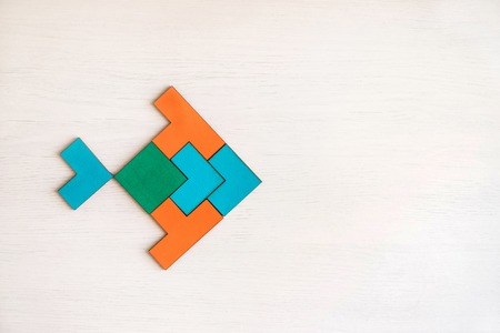 Color wooden tangram puzzle in fish shape on white wood background Banque d'images - 117350032