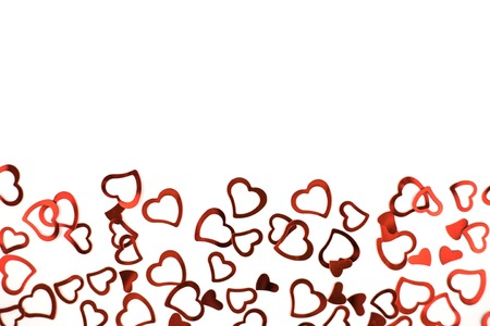 Valentines decoration of little red confetti hearts on white background. Festive concept.