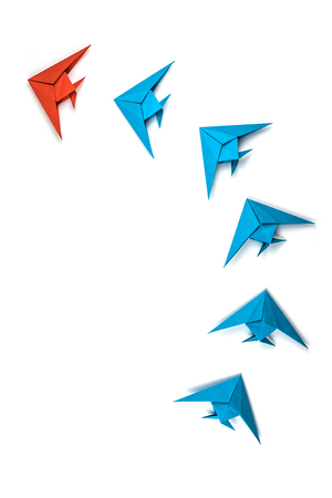 Paper origami fishes isolated on white background. Leadership and business concept.