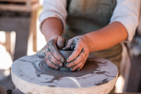 Potters hands are creating earthenware on potters wheel. Concept of natural materials, hand made and creativity. Stockfoto