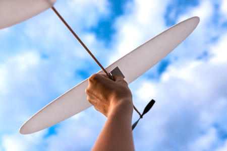 Little white toy plane in womans hand in sky. Concept of reaching goals. Standard-Bild