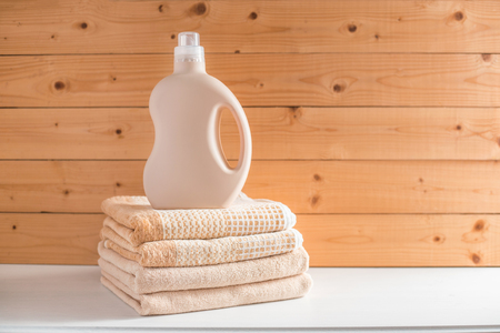 Gel for laundry washing in plastic bottle on a pile of fresh towels. Composition on white wooden shelf against wooden background.
