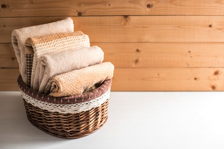 Basket with soft bath towels on wooden background. 免版税图像