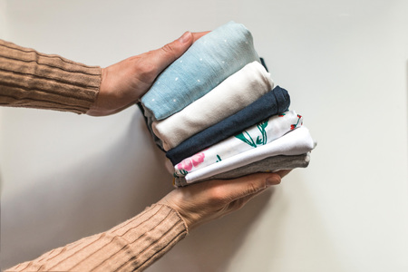 Housewife neatly folds a stack of clothes in hands. Concept of housekeeping. Imagens