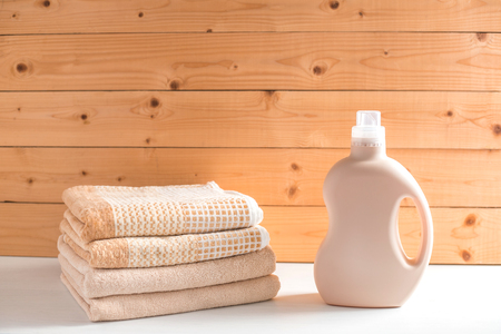 Gel for laundry washing in plastic bottle near a pile of fresh towels. Composition on white wooden shelf against wooden background.